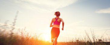 Women running into the sun enjoying her trail run